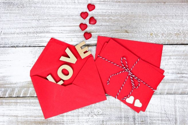 Red envelopes with hearts and LOVE on wood background
